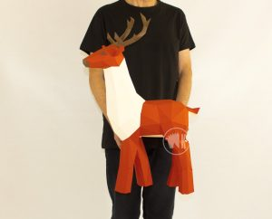 Person holding papercraft deer for scale image